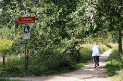 kollauwanderweg an der Grenze zu Hamburg Schnelsen; Wendlohstrasse / Radfahrerin.
