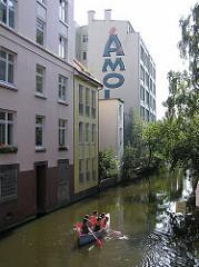 Kanu auf dem Mühlenkampkanal. Hamburger Industriearchitektur - Rückseite von Gewerbegebäuden.