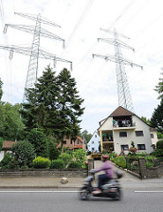 Wohnen unter Hochspannungsmasten - Einzelhäuser unter Stomleitungen in Hamburg Lohbrügge. Ein Motorroller auf der Strasse in Fahrt.