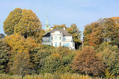Villa zwischen Herbstbäumen am Elbhang - Elbufer in Hamburg Nienstedten.