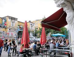 Blick über die Strasse Schulterblatt zum Gebäude der Roten Flora - Tische von Restaurants und Cafes auf dem Fussweg in der Sonne.