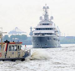Die Luxus-Motoryacht MAYAN QUEEN IV auf der Elbe im Hamburger Hafen - im Vordergrund der Schiff vom Hafenkapitän.