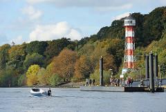Wald mit herbstlicher Färbung am Elbufer - Leuchtturm zwischen den Bäumen; ein Tuckerboot fährt am Anleger Wittenbergen vorbei.