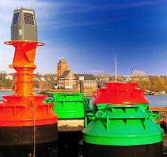 Frisch lackierte Fahrwassertonnen an Land, Hamburg Finkenwerder - im Hintergrund die Lotsenstation Seemannshöft.