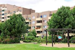 Begrünter Innenhof mit Spielplatz - mehrstöckige Wohngebäude mit Balkon - Wohnhäuser in Hamburg Steilshoop.