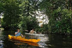 Das Ufer des Winterhuder Goldbekkanals ist dicht mit Bäumen und Büschen bewachsen.