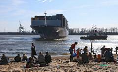 Gäste der Oevelgoenner Strandperle sitzen auf dem Elbstrand und beobachten ein Containerschiff bei der Wende im Hamburger Hafen.