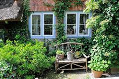Sitzbank aus Holz - Kopfsteinpflaster - Fenster mit blauem Rahmen eines alten Fischerhauses in Blankenese - Efeu an der Hausfassade.