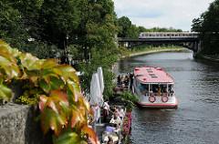Alsterschiff der Alsterrundfahrt legt an der Station Winterhuder Fährhaus an - Fahrgäste steigen in das Schiff ein.