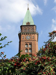 Kirchturm der Versöhnungskirche - rote Herbstfrüchte am Strauch.