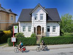 Gründerzeitvilla mit weisser Fassade und Stuckdekor - Radfahrer_in auf der Strasse. Stadtteilfotos aus Hamburg.