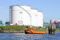 Hohe Tanks am Ufer der Wilhelmsburger Rethe; ein Festmacherboot an hat an den Holzdalben angelegt.