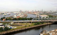 Eisenbahnbrücke über den Billhafen / Oberhafenkanal. In der Bildmitte der Baakenhafen; ein Frachter liegt am Versmannkai; dahinter eine Baustelle der Hafencity bei der Versmannstrasse.