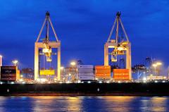 Nachtarbeit im Hamburger Hafen - beleuchtete Containerbrücken über einem Frachtschiff mit Containern beladen - Bilder aus dem Hamburger Hafen zur Blauen Stunde.