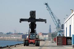 Teleskop Container Spreader am Ende des Versmannkais des Hamburger Baakenhafens. Im Hintergrund die Lagerschuppen des Hafenkais und der Turm des Michels, dem Hamburger Wahrzeichen. (2005)