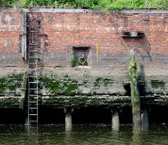 Alte Kaimauer/Ziegelmauer im Hamburger Hafen;  verrostete und verbogene Eisenleiter, eingelassener EIsenring und abgebrochener mit Gras bewachsener Holzdalben. Bei Niedrigwasser zeigen sich die Eichenstämmen auf denen die Kaianlage gegründet ist.