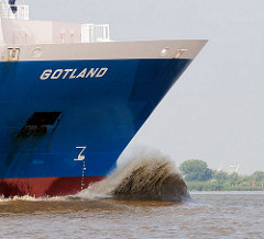 Schiffsbug GOTLAND in Fahrt auf der Elbe stromabwärts - am Wulstbug des Containerfeeders spritzt die Gischt hoch auf.