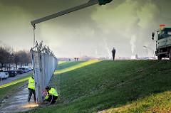 Ein Teil des ehem. Zollzauns wird mit einem Kran gesichert während Mitarbeiter den Eisenzaun mit einem Schneidbrenner abtrennt. Im Hintergrund Rauchwolken von Industrieanlagen im Hamburger Hafen.