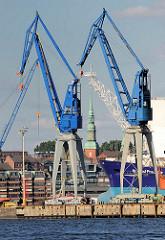 Hafenkräne / Werftkrane im Hamburger Hafen / Stadteil Steinwerder - im Hintergrund der Kirchturm der Kirche St. Pauli, die dem Stadtteil Sankt Pauli seinen Namen gegeben hat.
