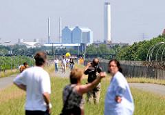 SpaziergängerInnen auf dem Klütjenfelder Hauptdeich in Hamburg Wilhelmsburg / Kleiner Grasbrook; rechts der Zollzaun, im Hintergrund das Heizkraftwerk Tiefstack.