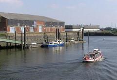 Eine Barkasse fährt aus dem Magdeburger Hafen Richtung Norderelbe - lks. der Liegeplatz des Hafenkapitäns; das Hafenboot liegt am Ponton des Versmannkais - auf der Kaianlage ein grosser Lagerschuppen. (2004)