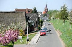 Wohnhäuser am Strassenrand hinter dem Deich von Hamburg Neuenfelde - St. Pankratiuskirche.