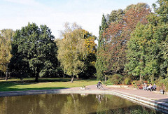Künstlicher See im Jacobi-Park von Hamburg Eilbek - Rentner sitzen in der Sonne auf der Parkbank - Bäume in der Herbstsonne.
