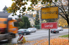 Hamburger Stadtgrenze, gelbes Grenzschild und rotes Stadtteilschild, Autoverkehr mit schnell fahrenden Autos.