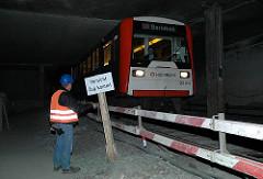 """Bauarbeiten an der U-Bahnstrecke am Berliner Tor - Bauarbeiter mit Schild """"vorsicht Zug kommt!"""""""