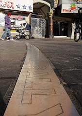 Eingelassenes Metallband im Boden des Beatle Platzes zwischen Reeperbahn und Grosser Freiheit auf Hamburg St. Pauli.