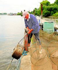 Zum Aufbewahren der lebenden Aale wird eine Stahltrommel aus dem Wasser geholt.