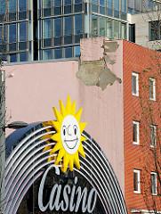 Lachende Sonne - Fassadenwerbung eines Spielcasinos an der Reeperbahn - abbröckelnder Putz einer Hausfassade - Glasfassade eines Neubaus.