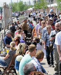 Spaziergänger in der Hafencity - Aussengastronomie am Grasbrookhafen - Tische und Stühle am Dalmannkai.