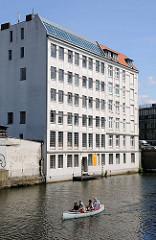 Rückseite eines Altbaus am Osterbekkanal / Barmbeker Strasse. Ein Kanu wird von den Kanuten Richtung Alster gepaddelt.