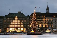 Nachtaufnahme beleuchteter Weihnachtsbaum auf der Binnenalster - Lichterschmuck an den Fassaden der Kaufhäuser - Weihnachtszeit in Hamburg.
