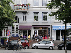 Strassencafés am Mühlenkamp in HH-Winterhude - Gäste sitzen in der Sonne an der Strasse.