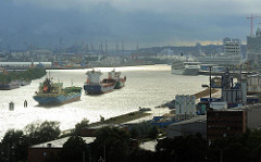Schwarze Gewitterwolken ziehen über Hamburg auf - letzte Sonnenstrahlen spiegeln sich im Wasser der Elbe.