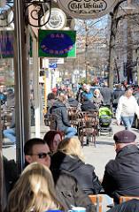 Strassencafés in der Langen Reihe in Hamburg St. Georg - Gäste sitzen an Tischen in der Sonne auf dem Fussweg.