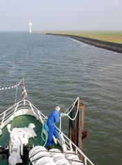 Ankunft des Fährschiffs auf Neuwerk - die Fähre legt an einem Dalben an - ein Arbeiter legt ein Tau um den Stahlpfahl.