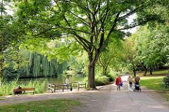 SpaziergängerInnen in der Parkanlage am Weiher in Hamburg Eimsbüttel . Hohe Bäume am Wasser des Teichs.