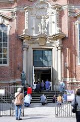 Gottesdienst am Sonntag - Gläubige knien vor dem Eingang der katholischen St. Josephs-Kirche; Touristen sehen zu. Bilder aus Hamburg St. Pauli.