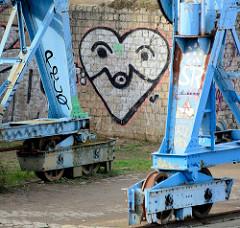 Graffiti - Herz auf der Ziegelmauer; Laufrollen auf Schienen am Billehafen in Hamburg Rothenburgsort.