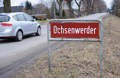 Bilder aus dem Hamburger Stadtteil Ochsenwerder - Bezirk Hamburg Bergedorf. Rotes Stadtteilschild mit weisser Schrift an der Strasse.