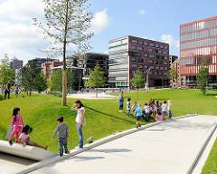 Blick über den Sandtorpark zu der modernen Architektur der Wohnhäusern und Bürogebäude am Sandtorkai der Hamburger Hafencity.