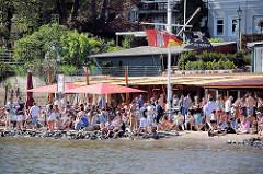 Dichtes Gedränge am Elbufer - Menschen sonnen sich am Elbufer - andere stehen in der Schlange bei der Strandperle in Hamburg Othmarschen.