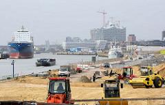 Bauarbeiten am Kirchenpauerkai in der Hamburger Hafencity - Planierraupen schütten Sand auf; ein Binnenschiff fährt elbabwärts - im Hintergrund die Baustelle der Elbphilharmonie.