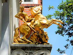 Goldener Ritter St. Georg mit Drachen in Hamburg St. Georg - Skulptur an einer Hausfassade.