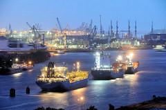 Beleuchtete Schiffe im Hamburger Hafen auf der Elbe - im Hintergrund die Hafen und Werftkräne.