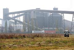 Aluminiumhütte in Hamburg Altenwerder, Förderanlage und Werksgebäude; ein Trecker mäht ein Wiese am Dradenauhafen.