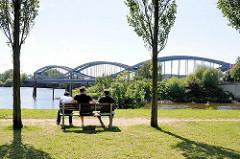 Elbpark von Entenwerder - Grünanlage in Hamburg Rothenbursort - Besucher sitzen zwischen Bäumen auf einer Parkbank und blicken auf die Elbe und die geschwungenen Stahlbögen der Norderelbbrücke.